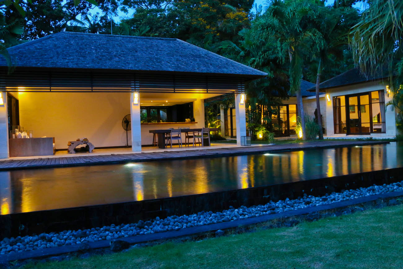 The swimming pool at night with the villa living room as the background